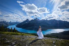 Hiking in Canadian Rockies. Woman on mountain top looking at scenic view of turquoise lake and mountains peaks. West Wind Pass. Kananaskis. Alberta. Canada stock photos