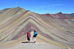 Hiking the Cerro Colorado - aka Rainbow Mountain - in Peru. An unidentified peruvian couple with typical clothes hiking on the Cerro Colorado, near to Cusco royalty free stock photo