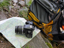 Hiking concept. Hiking outdoor sports and nature expedition concept with bagpack topographic map and camera Stock Photography