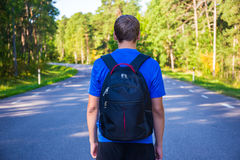 Hiking concept - back view of man walking on forest road. Hiking concept - back view of man with backpack walking on forest road Stock Photos