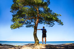 Hiking concept - hiker with backpack on the beach Royalty Free Stock Image