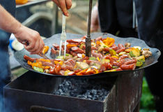 Active recreation - sausage, mushrooms and grilled vegetables on the grill Stock Images