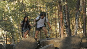 Hiking couple climbs on the rock. Young hiking couple climbing on the rock at the forest. Caucasian bearded man helping his girlfriend to climb on the rock. Fit stock video footage