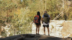Hiking couple comes to the cliff. Young hiking couple coming to the cliff at the mountains. Brunette man and woman carrying hiking backpacks. Slim girl standing stock video