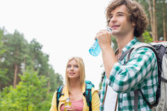 Hiking couple drinking energy drinks in forest Stock Image