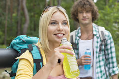 Hiking couple with energy drinks in forest Stock Photography