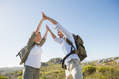 Hiking couple high fiving on mountain terrain. On a sunny day Stock Photo