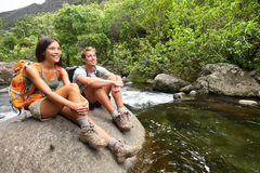 Hiking couple hikers in outdoor activity on Hawaii. Hiking couple of hikers in outdoor activity wearing backpacks relaxing. Woman and men hiker looking with Royalty Free Stock Photography