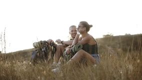 Hiking couple - hikers resting on a hill. Young woman and man hiker sitting on the ground enjoying view smiling happy stock footage