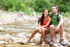 Hiking couple - hikers resting in Zion Park. Hiking couple - hikers resting in Zion National Park. Young women and men hiker sitting by river water creek Royalty Free Stock Images