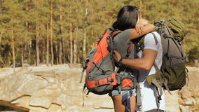 Hiking couple hugs near the cliff. Caucasian hiking couple hugging near the cliff. Gorgeous brunette girl dressed in shorts cuddling her boyfriend. Young bearded stock video