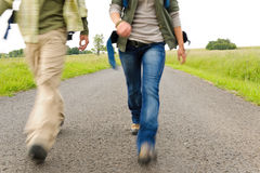 Hiking couple legs backpack on asphalt road Stock Images