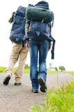 Hiking couple legs backpack on asphalt road Royalty Free Stock Image