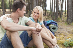 Hiking couple looking at each other while relaxing in forest Stock Image