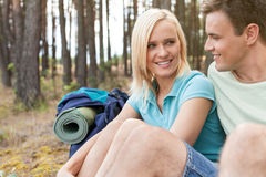 Hiking couple looking at each other while relaxing in forest Stock Photos