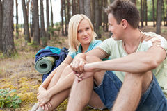 Hiking couple looking at each other while relaxing in forest Stock Photo