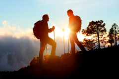 Hiking couple looking enjoying sunset view on hike. During trek in mountain nature landscape at sunset. Active healthy couple doing outdoor activities royalty free stock photos
