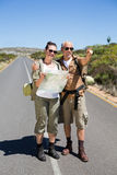 Hiking couple looking at map on the road and pointing ahead Stock Photography