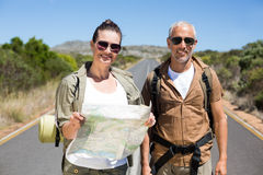Hiking couple looking at map on the road Royalty Free Stock Photography