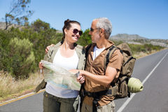 Hiking couple looking at map on the road Royalty Free Stock Image