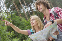 Hiking couple with map discussing over direction in forest Stock Photography