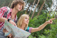 Hiking couple with map discussing over direction in forest Stock Image