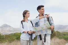 Hiking couple with map pointing ahead on mountain terrain Stock Image