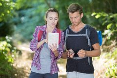 Hiking couple with map in wilderness Stock Images