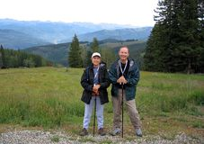 Hiking Couple in the Mountains. A middle-aged couple relaxes while they hike together in the mountains Stock Images