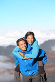Hiking couple piggybacking happy Stock Photo