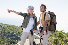 Hiking couple pointing and looking at mountain summit Stock Photography