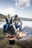 Hiking Couple Preparing Bonfire On Lakeshore Stock Photos