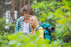 Hiking couple reading map together in forest Stock Photos
