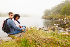 Hiking couple relaxing by the edge of a lake, looking to camera Stock Photo