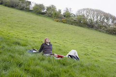 Hiking Couple Relaxing On Grass Royalty Free Stock Images
