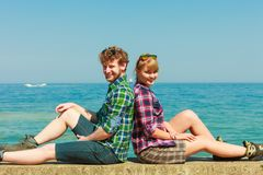 Hiking couple relaxing on sea coast. Summer vacation and traveling concept. Young hiking couple women men relaxing after hike on sea shore enjoying sunlight Royalty Free Stock Images