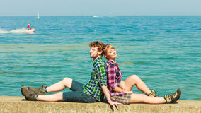 Hiking couple relaxing on sea coast. Summer vacation and traveling concept. Young hiking couple women men relaxing after hike on sea shore enjoying sunlight Royalty Free Stock Photos