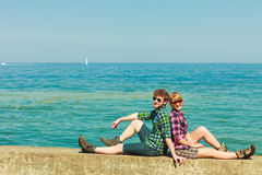 Hiking couple relaxing on sea coast. Summer vacation and traveling concept. Young hiking couple women men relaxing after hike on sea shore enjoying sunlight Royalty Free Stock Photography