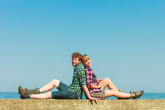 Hiking couple relaxing on sea coast. Summer vacation and traveling concept. Young hiking couple women men relaxing after hike on sea shore enjoying sunlight Royalty Free Stock Photo