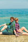 Hiking couple relaxing on sea coast. Summer vacation and traveling concept. Young hiking couple women men relaxing after hike on sea shore enjoying sunlight Stock Image