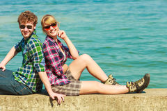 Hiking couple relaxing on sea coast. Summer vacation and traveling concept. Young hiking couple women men relaxing after hike on sea shore enjoying sunlight Royalty Free Stock Image