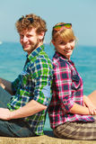 Hiking couple relaxing on sea coast. Summer vacation and traveling concept. Young hiking couple women men relaxing after hike on sea shore enjoying sunlight Stock Images