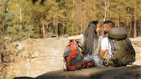 Hiking couple sits on the edge of the cliff. Beautiful hiking couple sitting on the edge of the cliff. Pretty brunette girl touching her nice long hair near her stock footage
