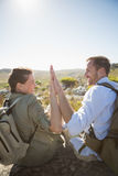 Hiking couple sitting on mountain terrain high fiving. On a sunny day Stock Photo