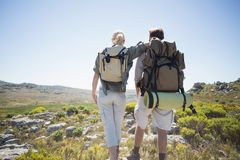 Hiking couple standing on mountain terrain. On a sunny day stock photo