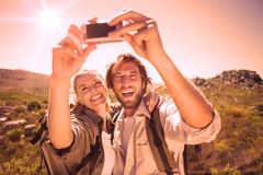 Hiking couple standing on mountain terrain taking a selfie Stock Photo