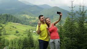 Hiking couple standing on mountain terrain taking a selfie on a sunny day. Couple standing on mountain terrain taking a selfie on a sunny day stock video