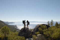 Hiking Couple Standing On Rock At Coast Stock Photography
