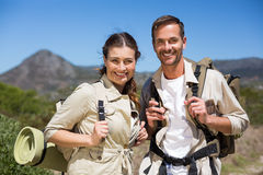 Hiking couple standing and smiling at camera on country terrain Royalty Free Stock Image