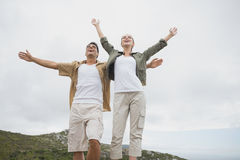 Hiking couple stretching hands on mountain terrain Stock Photo